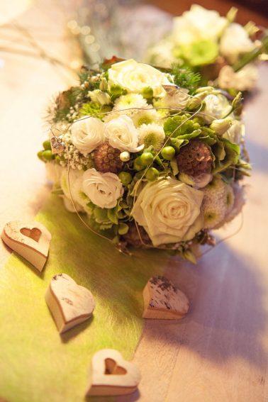 Hochzeitsreportage-Tischdekoration-Ehepaar-Holzherzen-Rosen-Nahaufnahme-Fokus