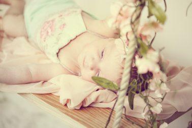 baby-foto-auf-holzschaukel-mit-blumenranken